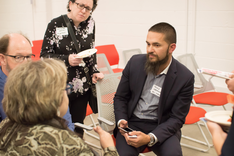 CEO Tony Abrahams talking to a group of three