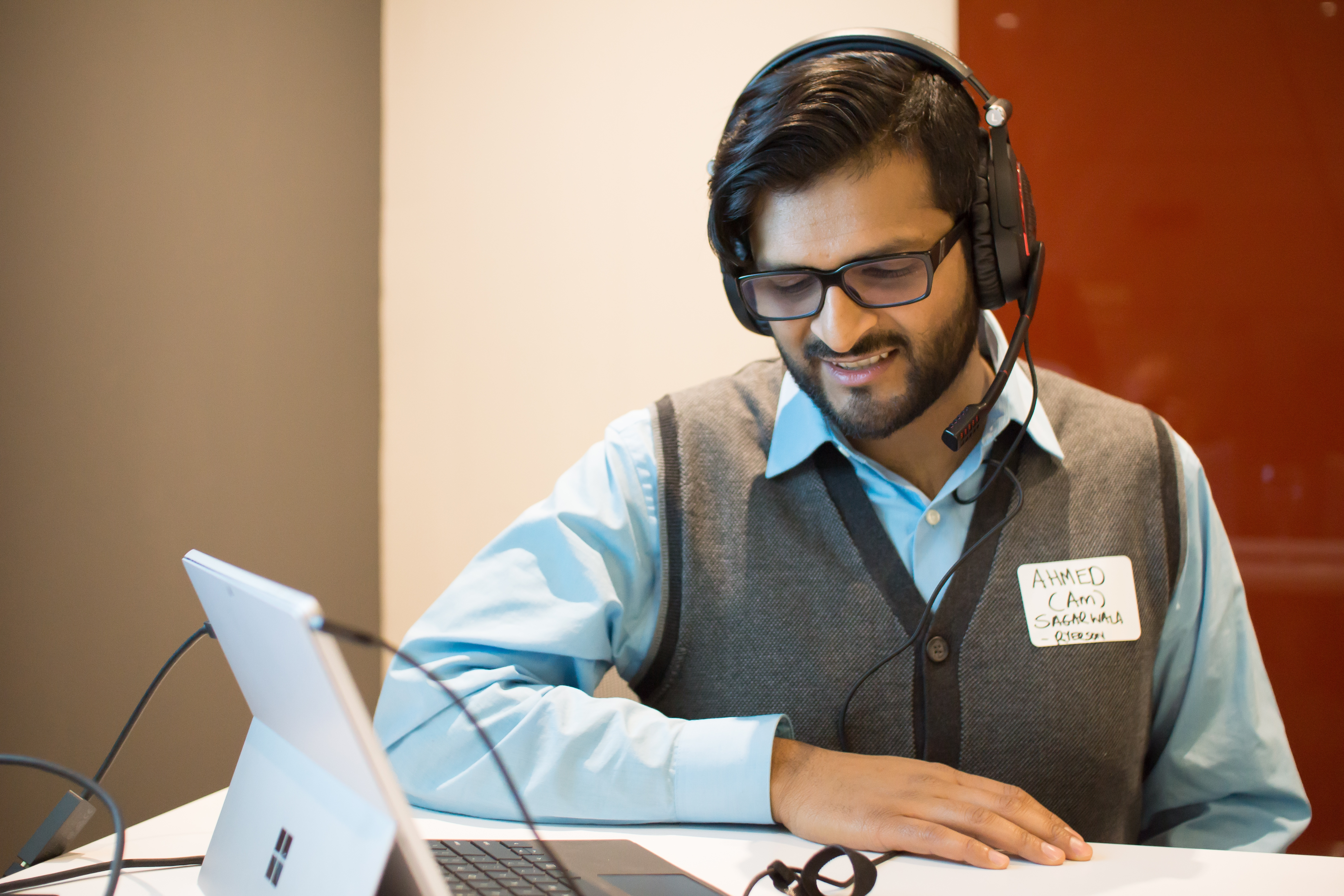 a smiling male looking at a laptop screen wearing a headset with a microphone