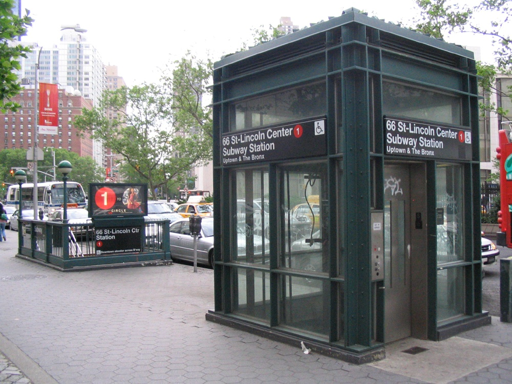 A street elevator leading to the 66 St-Lincoln Center Subway Station. The elevator sits near the stairs down to the subway station.