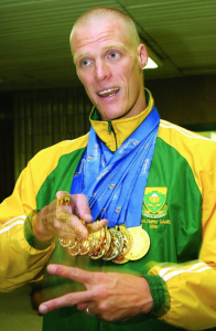 Terrence Parkin wearing a green and yellow tracksuit and several gold medals hanging around his neck.