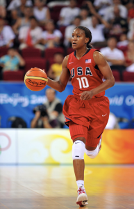 Tamika Catching in red USA basketball jersey. Running down the court while bouncing a basketball.