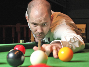 Close up of Carl Morris lining up a shot on the pool table.