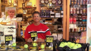Brad Minns wearing red sweater standing behind tennis shop counter and holding his book.