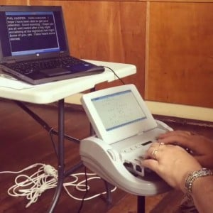 Image of laptop with captions and hands on a stenocaptioning machine.