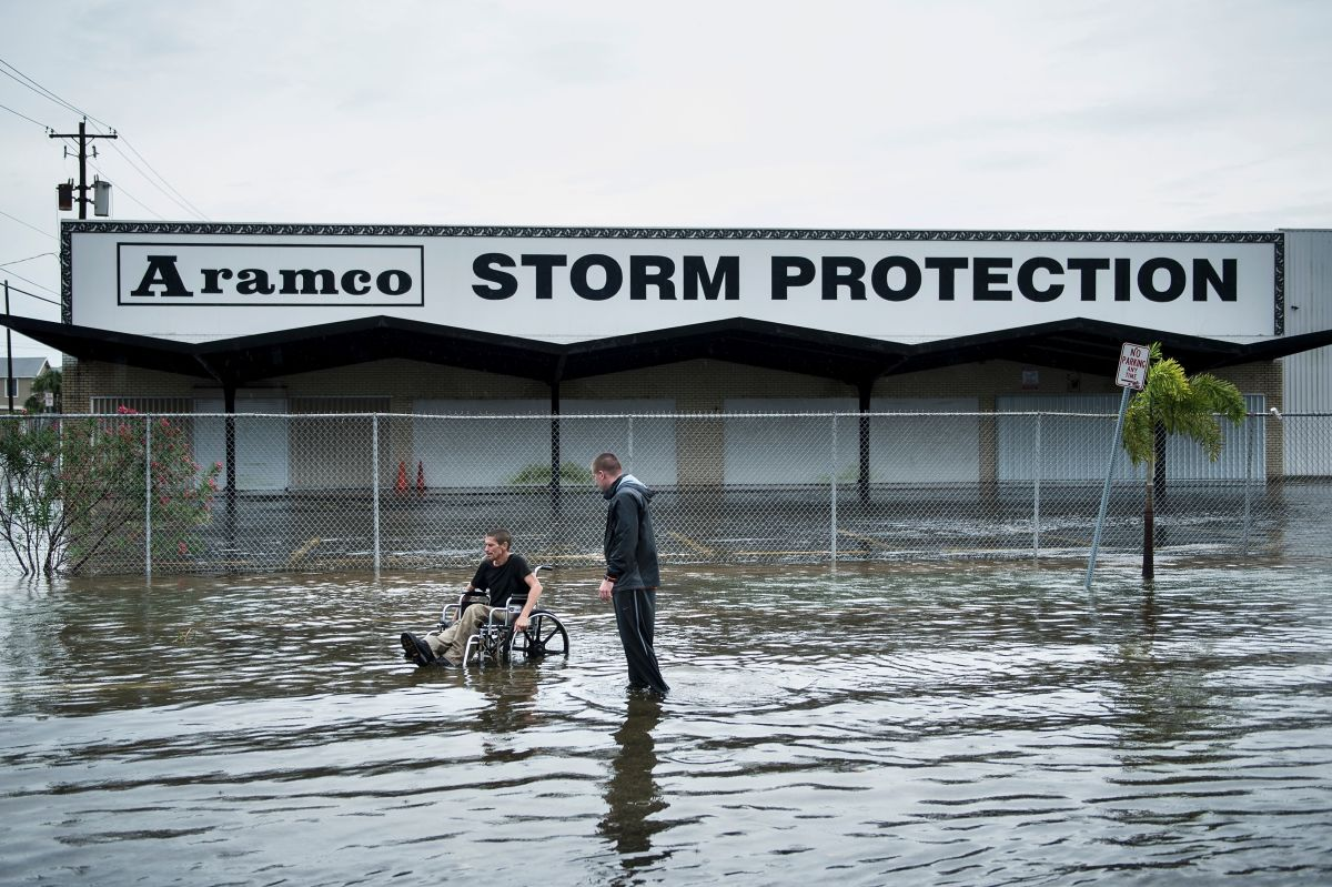 """Image from the Floods in Texas  in 2017. Two men wade through flood water in front of a store front. One man is in a wheelchair. The store front sign says """"Aramco Storm Protection""""."""