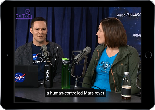 """An ipad displaying a discussion between NASA employees. The closed captions say: """"a human-controlled Mars rover"""""""