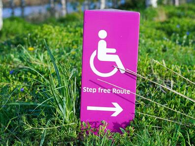 Pink Disability Sign Pointing to the Right